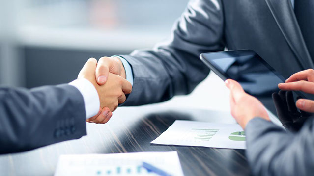 Business men shaking hands after agreeing a Business Loan.